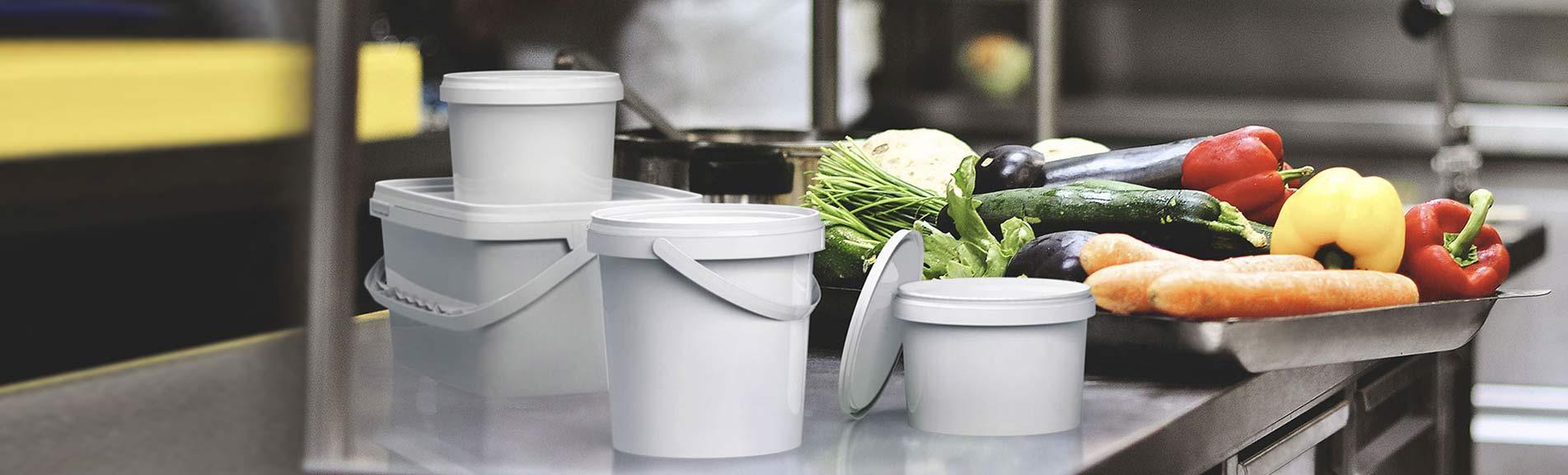 Wiadra i opakowania plastikowe w pobliżu warzyw